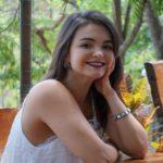 Jessica veste camisa branca sem mangas, leva a mão esquerda junto ao rosto e sorri para a foto.