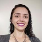 Aline sorri para foto e usa cordão e camisa cinza