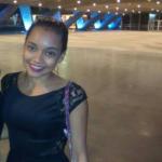 Flavia veste vestido preto e sorri para foto, ao fundo, pilastras iluminadas em azul