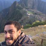 Gustavo usa um casaco e vira sua cabeça para tirar uma fotografia sorrindo. Ao fundo, montanhas com grande área verde.